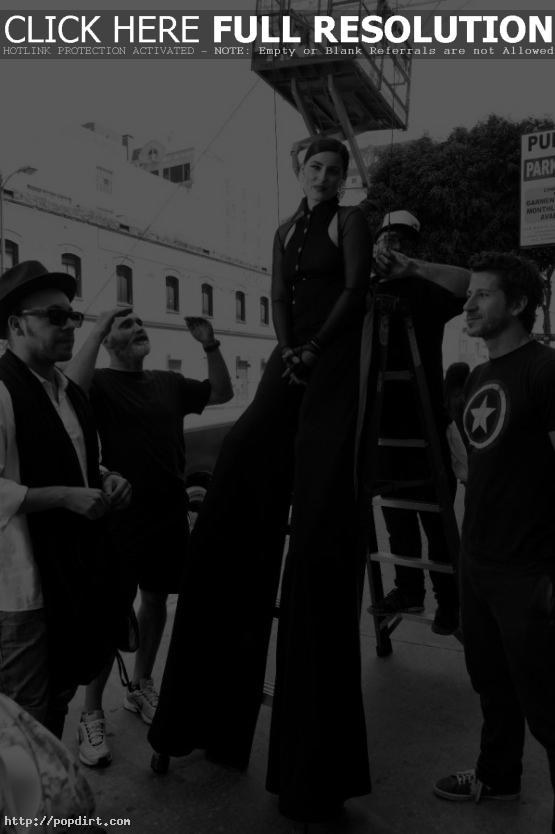 Nelly Furtado standing on stilts during her 'Big Hoops (The Bigger The Better)' music video shoot